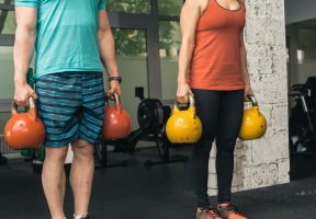 man and a woman carrying dumbbells at the gym